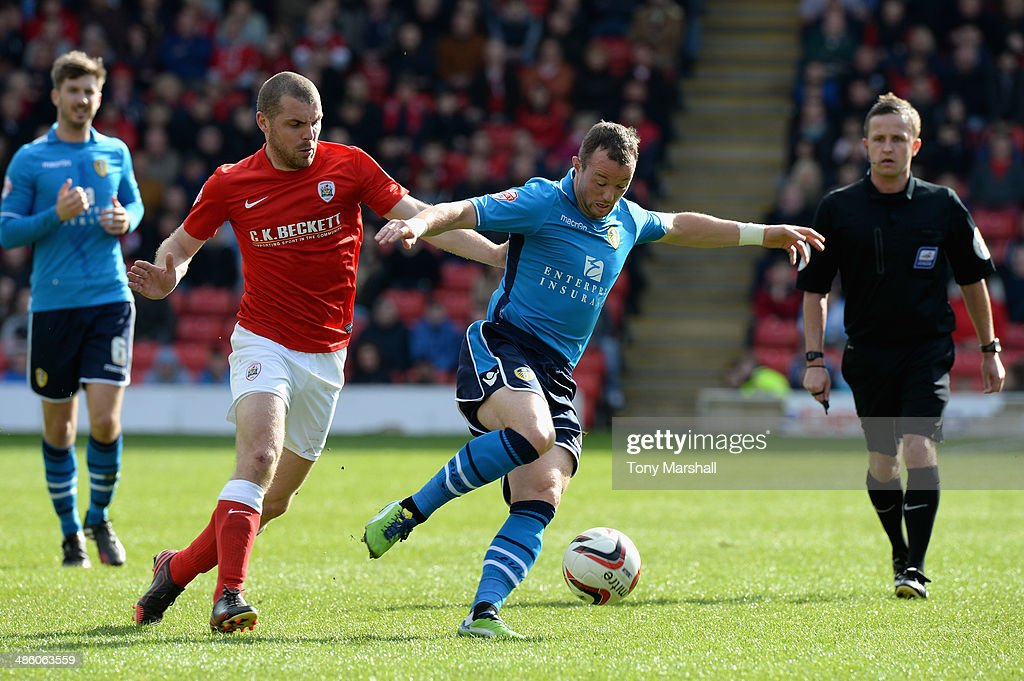 Stephen Dawson of Barnsley tackles <a gi-track='captionPersonalityLinkClicked' href=/galleries/search?phrase=Noel+Hunt&family=editorial&specificpeople=3580775 ng-click='$event.stopPropagation()'>Noel Hunt</a> of Leeds United during the Sky Bet Championship match between Barnsley and Leeds United at Oakwell on April 19, 2014 in Barnsley, England,