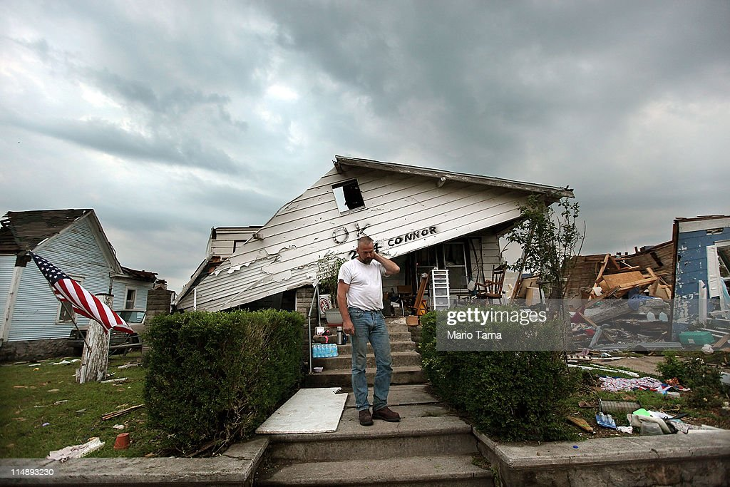 Stephen Dickson stands in front of his parent's home while on the lookout for looters at dusk five days after a massive tornado passed through the town killing at least 132 people on May 27, 2011 in Joplin, Missouri. Although the house has no roof, Dickson sometimes sleeps in the home to protect it from looting. The town continues the process of recovering from the storm which damaged or destroyed an estimated 8,000 structures.