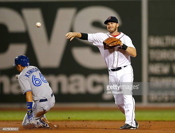 Stephen Drew of the Boston Red Sox attempts a double play as Munenori Kawasaki of the Toronto Blue Jays is out at second base in the sixth inning at...