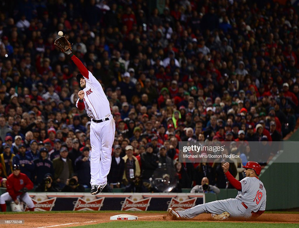 <a gi-track='captionPersonalityLinkClicked' href=/galleries/search?phrase=Stephen+Drew&family=editorial&specificpeople=757520 ng-click='$event.stopPropagation()'>Stephen Drew</a> #7 of the Boston Red Sox attempts to catch an errant throw as <a gi-track='captionPersonalityLinkClicked' href=/galleries/search?phrase=Jon+Jay+-+Baseball+Player&family=editorial&specificpeople=5734285 ng-click='$event.stopPropagation()'>Jon Jay</a> #19 of the St. Louis Cardinals slides into third base in the seventh inning of Game Two of the World Series on October 24, 2013 at Fenway Park in Boston, Massachusetts. Jay would score on the play.