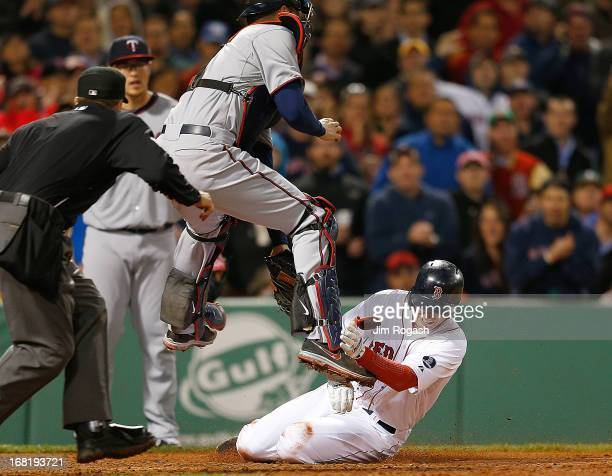 Stephen Drew of the Boston Red Sox is out at the plate as Joe Mauer of the Minnesota Twins leaps for a throw and tags out Drew in the 5th inning at...