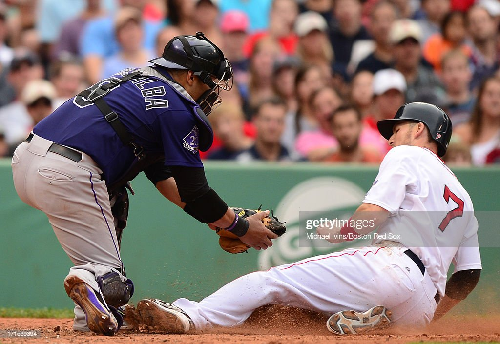 Stephen Drew #7 of the Boston Red Sox is tagged out at the plate by Yorvit Torrealba #8 of the Colorado Rockies in the sixth inning on June 26, 2013 at Fenway Park in Boston, Massachusetts.