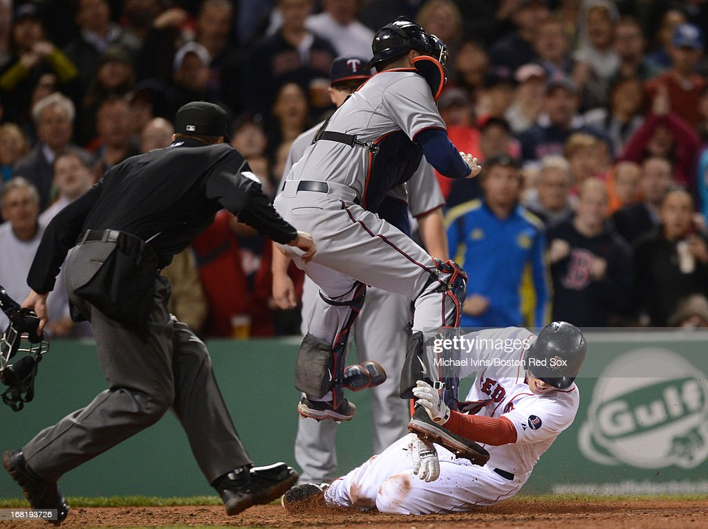 Stephen Drew #7 of the Boston Red Sox slides into Joe Mauer #7 of the Minnesota Twins before being called out on the play by home plate umpire Cory Blaser #89 in the fifth inning on May 6, 2013 at Fenway Park in Boston, Massachusetts.