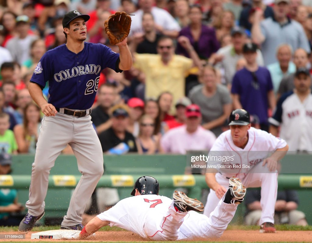 Stephen Drew #7 of the Boston Red Sox slides into third with a triple ahead of the throw to Nolan Arenado #28 of the Colorado Rockies in the sixth inning on June 26, 2013 at Fenway Park in Boston, Massachusetts.