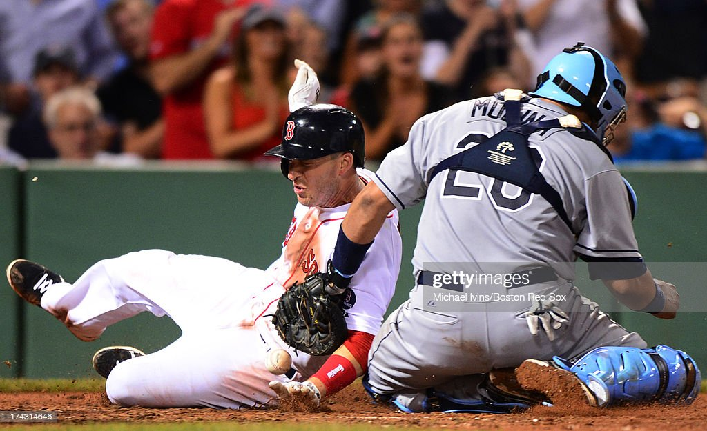 Stephen Drew #7 of the Boston Red Sox slides through an attempted tag by Jose Molina #28 of the Tampa Bay Rays in the ninth inning on July 23, 2013 at Fenway Park in Boston, Massachusetts.