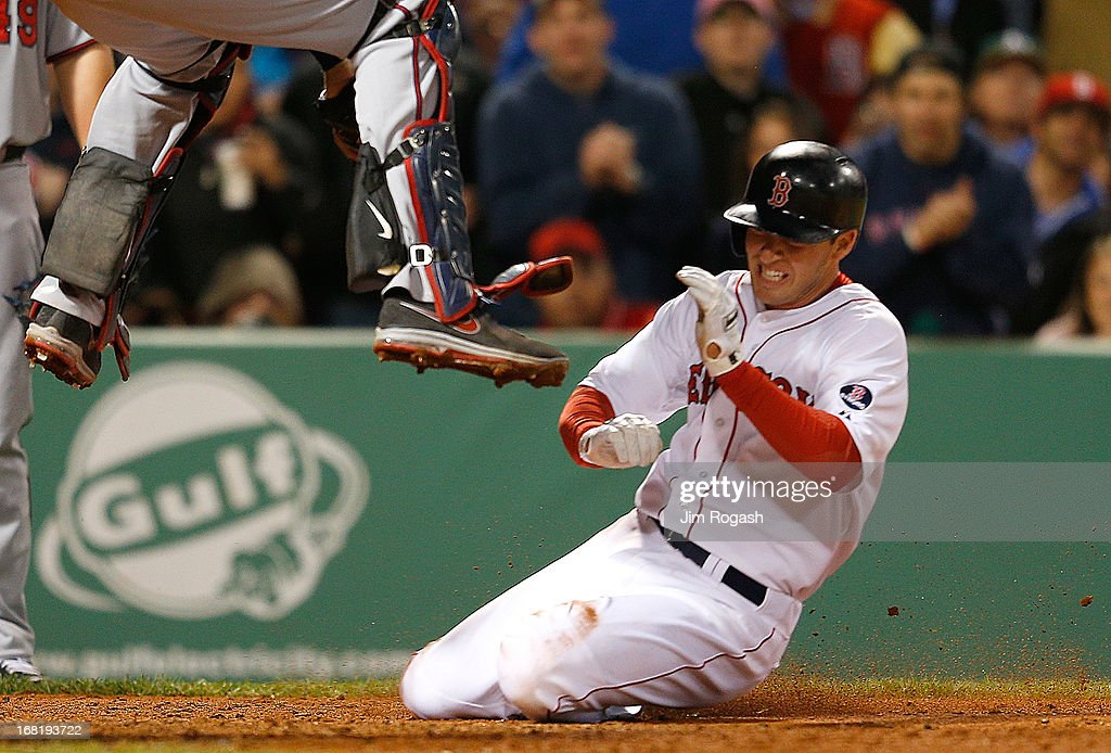 Stephen Drew #7 of the Boston Red Sox slides toward home as Joe Mauer #7 of the Minnesota Twins leaps for a throw in the 5th inning at Fenway Park on May 6, 2013 in Boston, Massachusetts. Drew was tagged out on the play.