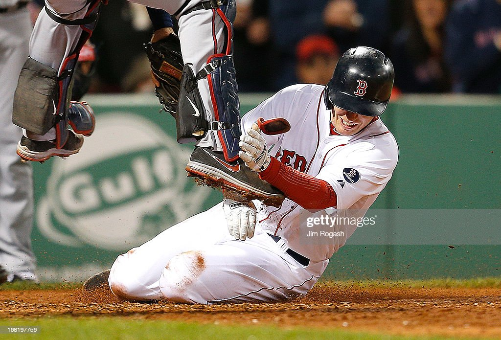 Stephen Drew #7 of the Boston Red Sox slides toward home as Joe Mauer #7 of the Minnesota Twins leaps for a throw in the 5th inning the at Fenway Park on May 6, 2013 in Boston, Massachusetts. Drew was tagged out on the play.