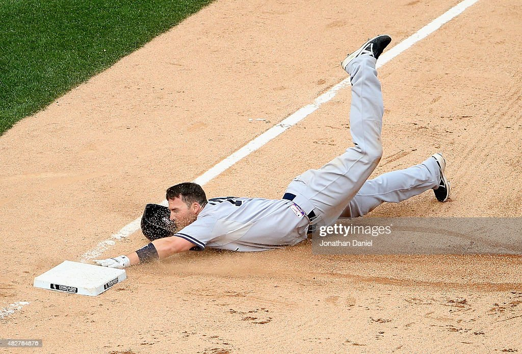 Stephen Drew #14 of the New York Yankees dives into third base after hitting a two-run triple in the 7th inning against the Chicago White Sox at U.S. Cellular Field on August 2, 2015 in Chicago, Illinois.