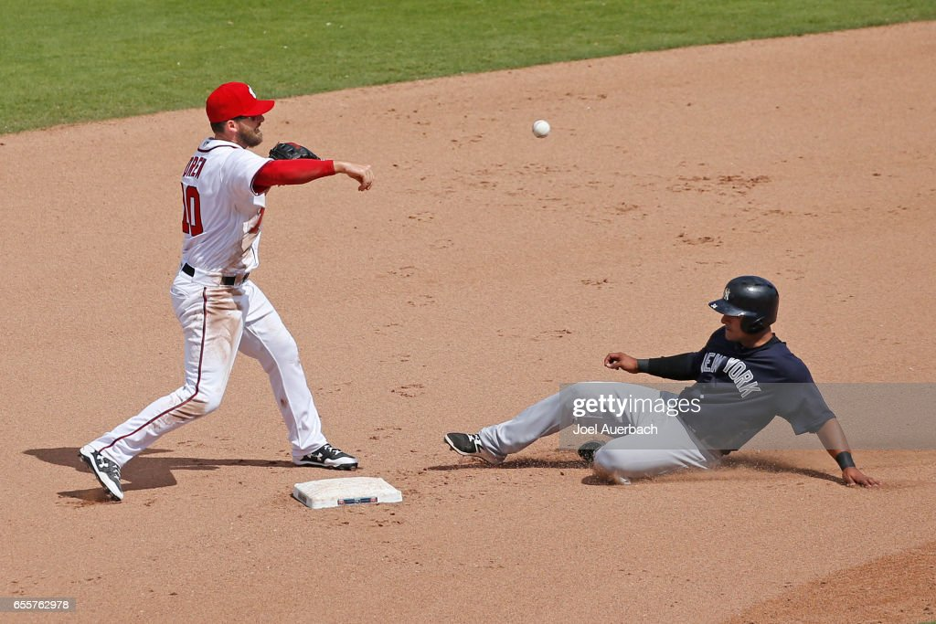 Stephen Drew #10 of the Washington Nationals gets Donovan Solano #34 of the New York Yankees out at second but can't complete the double play in the seventh inning during a spring training game at The Ballpark of the Palm Beaches on March 20, 2017 in West Palm Beach, Florida. The Yankees defeated the Nationals 9-3.