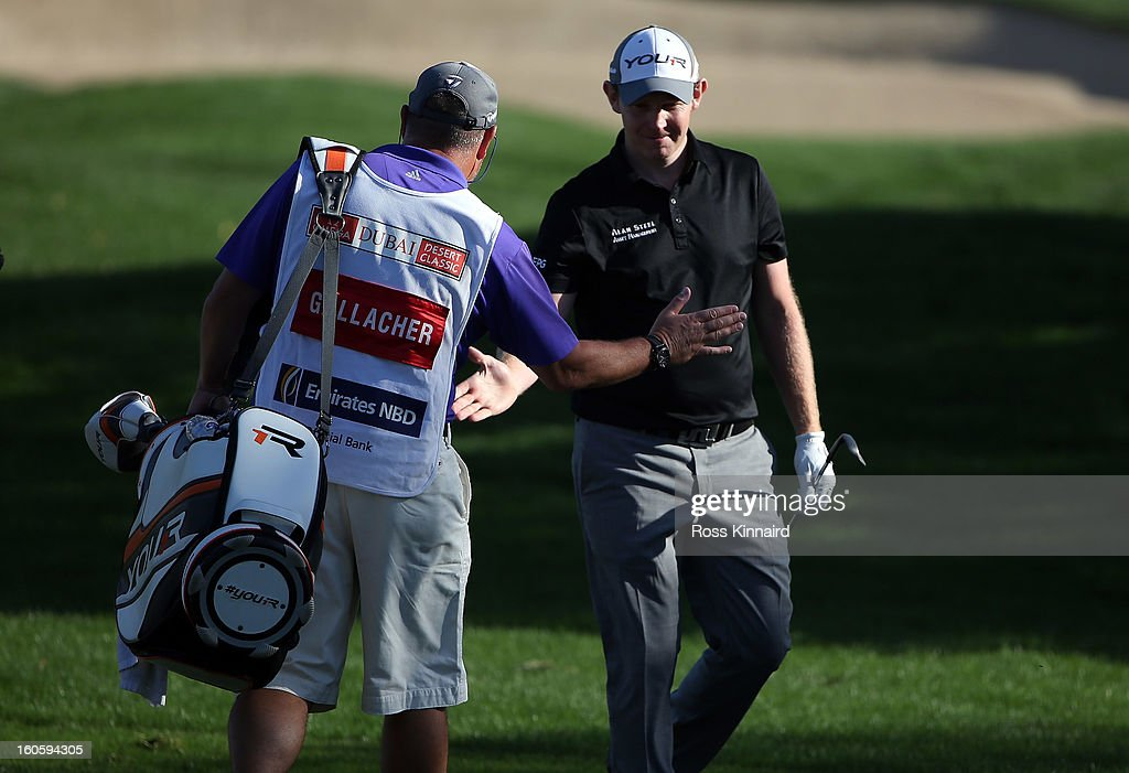 Stephen Gallacher of Scotland celebrates with his caddie Damien Moore after he holes out with his second shot for an eagle two on the par four 16th hole during the final round of the Omega Dubai Desert Classic on February 3, 2013 in Dubai, United Arab Emirates.