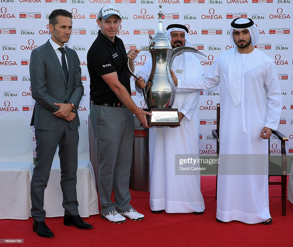 Stephen Gallacher of Scotland is presented with the trophy by (L) Sheikh Majid bin Mohammed bin Rashid al Maktoum, as Mohammed Juma Buamaim the Deputy Chairman and CEO of Golf in Dubai (C), looks on, during the final round of the 2013 Omega Dubai Desert Classic on the Majilis Course at the Emirates Golf Club on February 3, 2013 in Dubai, United Arab Emirates.