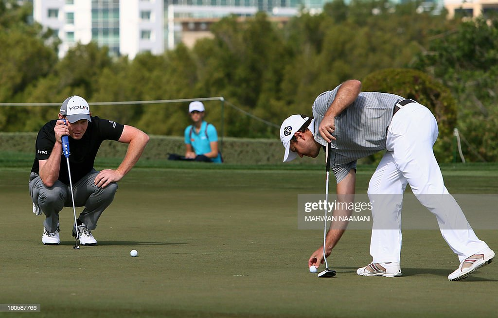 Stephen Gallacher (L) of Scotland lines a putt as Richard Sterne of South Africa puts his ball on the green on the fouth and last round of the Omega Dubai Desert Classic in Dubai, on February 3, 2013.