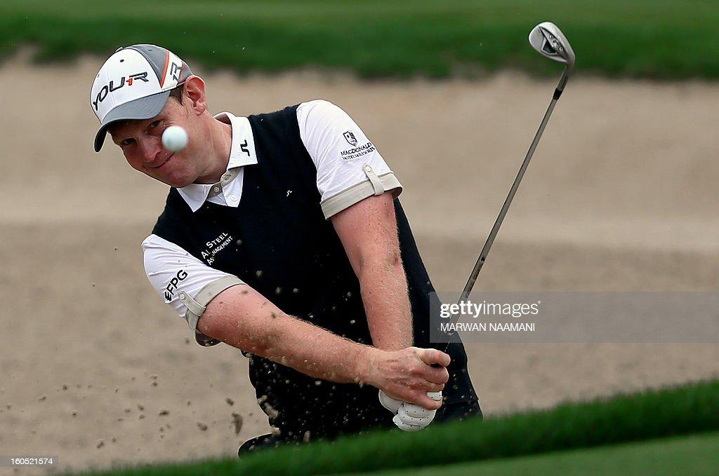 Stephen Gallacher of Scotland plays a bunker shot during the third round of the Dubai Desert Classic golf tournament in Dubai on February 2, 2013.