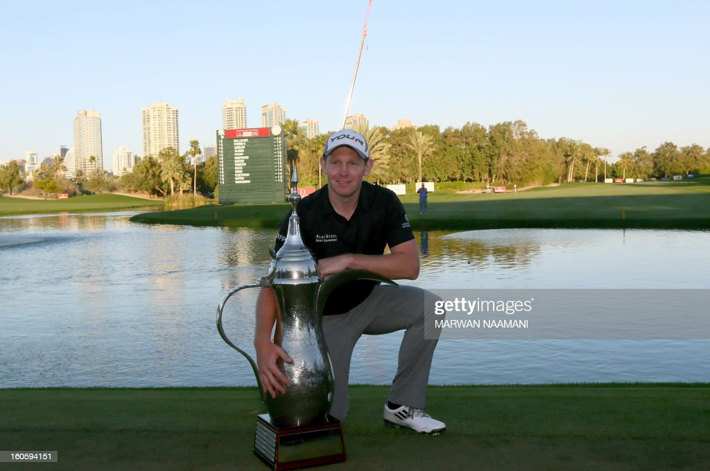 Stephen Gallacher of Scotland poses with the trophy after winning the Dubai Desert Classic in Dubai, on February 3, 2013. Gallacher fired a timely eagle two on the par-4 16th hole and comfortably won the $2.5 million Omega Dubai Desert Classic in the end by three shots. AFP PHOTO/MARWAN NAAMANI