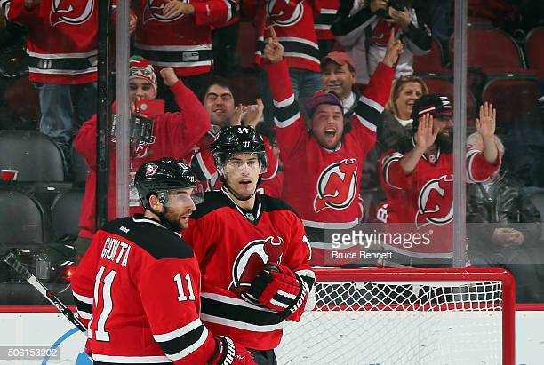 Stephen Gionta and Adam Henrique of the New Jersey Devils celebrate Henrique's empty net goal against the Ottawa Senators at the Prudential Center on...