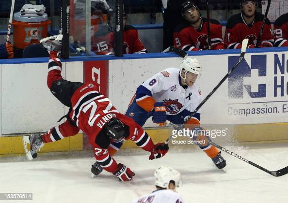 Stephen Gionta of the Albany Devils is upended as Nathan McIver of the Bridgeport Sound Tigers passes the puck at the Webster Bank Arena at Harbor...