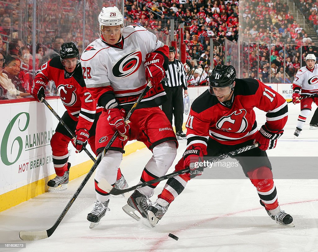 Stephen Gionta #11 of the New Jersey Devils and Alexander Semin #28 of the Carolina Hurricanes fight for the puck at the Prudential Center on February 12, 2013 in Newark, New Jersey.The Carolina Hurricanes defeated the New Jersey Devils 4-2.