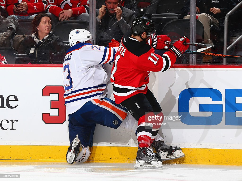 Stephen Gionta of the New Jersey Devils and Matt Hendricks of the Edmonton Oilers battle for position during the game at the Prudential Center on...