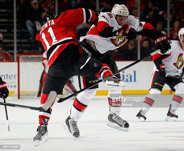 Stephen Gionta of the New Jersey Devils and Mika Zibanejad of the Ottawa Senators collide at the Prudential Center on December 18 2013 in Newark New...