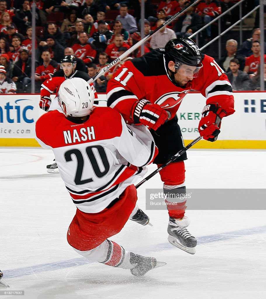 Stephen Gionta of the New Jersey Devils checks Riley Nash of the Carolina Hurricanes during the second period at the Prudential Center on March 1...