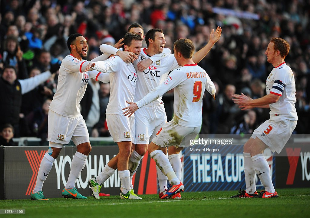 Stephen Gleeson of MK Dons (2L) celebrates with team mates as he scores their first goal during the FA Cup with Budweiser Second Round match between MK Dons and AFC Wimbledon at StadiumMK on December 2, 2012 in Milton Keynes, England. This match is the first meeting between the two teams following the formation of AFC Wimbledon (the football club formed in 2002 by supporters unhappy with their club's relocation to Milton Keynes) and the MK Dons (which Wimbledon F.C. controversially became).