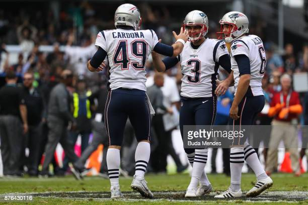 Stephen Gostkowski of the New England Patriots celebrates with Joe Cardona and Ryan Allen after kicking a field goal against the Oakland Raiders...