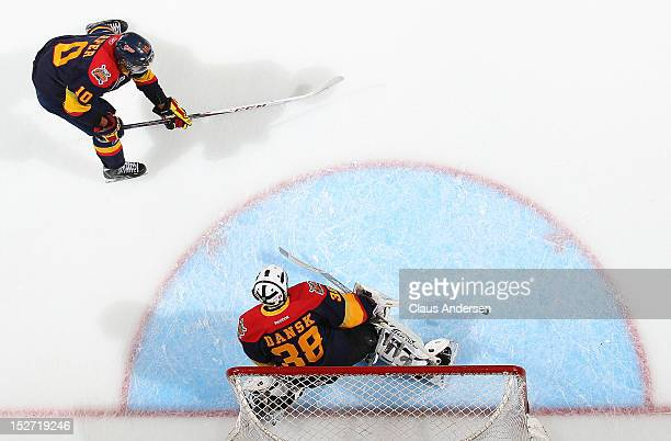 Stephen Harper of the Erie Otters fires a shot on teammate Oscar Dansk in the warmup prior to an OHL game against the London Knights on September 21...
