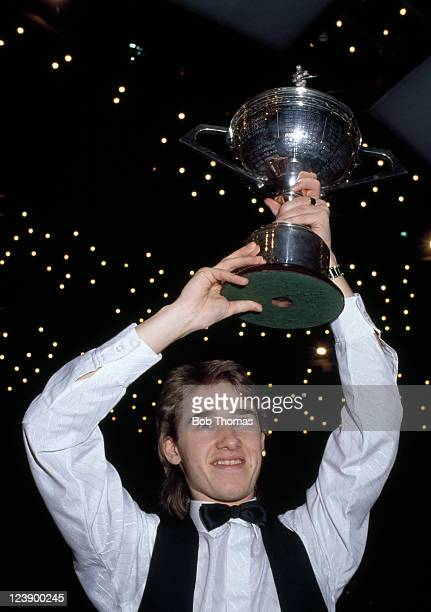 Stephen Hendry of Scotland holds aloft the trophy after defeating Jimmy White of England 1812 in the World Snooker Championship Final at the Crucible...