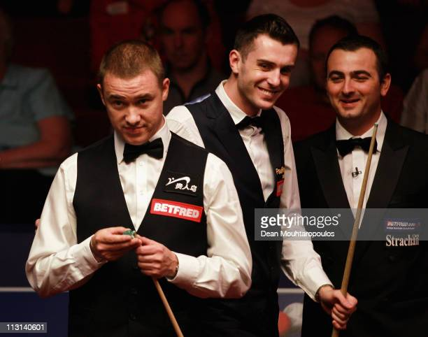 Stephen Hendry of Scotland looks to play a shot in the round two game against Mark Selby of England puts his hands on his sholder on day nine of the...