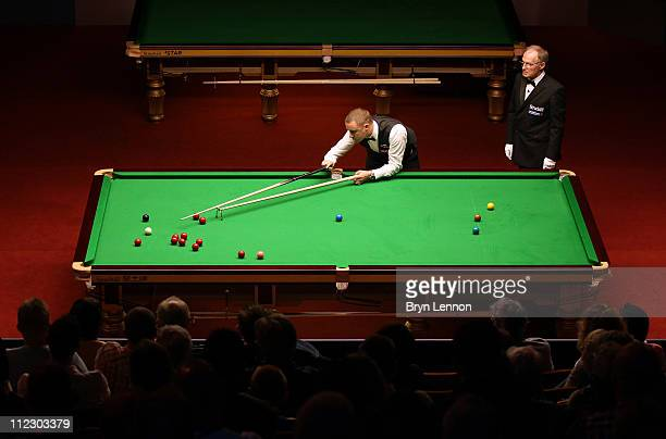 Stephen Hendry of Scotland plays a shot against Joe Perry of England in his round one game on day two of the Betfredcom World Snooker Championship at...