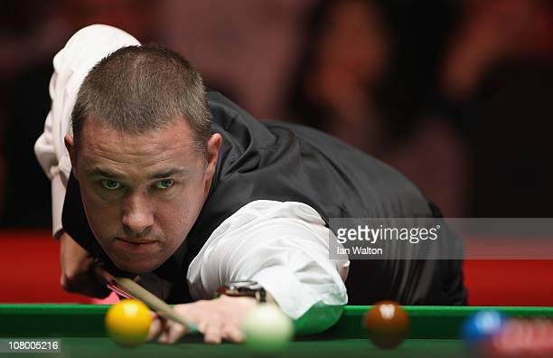 Stephen Hendry of Scotland plays a shot against Neil Robertson of Australia in Round One of The Ladbrokesmobile Masters on Day 4 at Wembley Arena on...