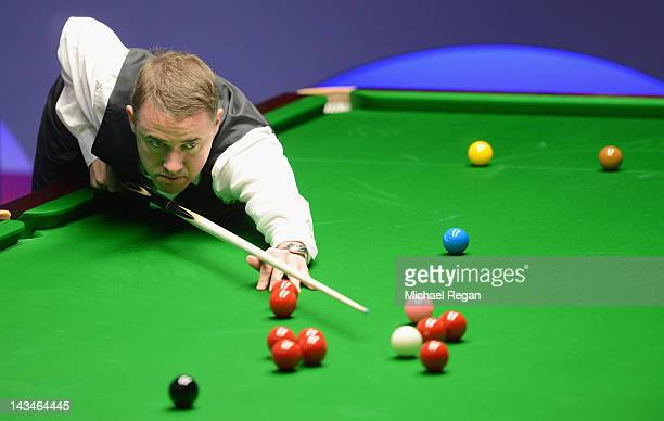 Stephen Hendry of Scotland plays a shot in his round two match against John Higgins of Scotland during the Betfredcom World Snooker Championship at...