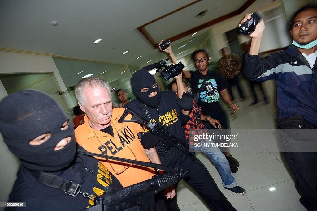 Stephen Henri Lubbe (2nd L) of South Africa is escorted by security at the customs office in Denpasar on Bali island on February 14, 2014. Lubbe was arrested on February 9 carrying 1540 grams of methamphetamine hidden in his luggage at Bali International Airport in Indonesia. AFP PHOTO / SONNY TUMBELAKA
