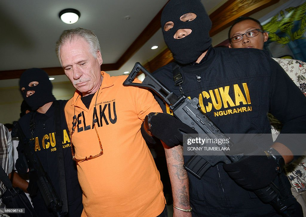 Stephen Henri Lubbe (L) of South Africa is escorted by security at the customs office in Denpasar on Bali island on February 14, 2014. Lubbe was arrested on February 9 carrying 1540 grams of methamphetamine hidden in his luggage at Bali International Airport in Indonesia. AFP PHOTO / SONNY TUMBELAKA