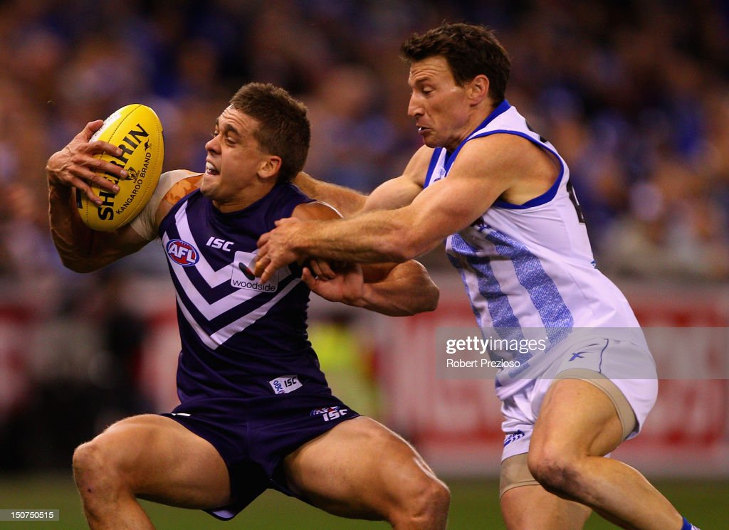 Stephen Hill of the Dockers is tackled by <a gi-track='captionPersonalityLinkClicked' href=/galleries/search?phrase=Brent+Harvey&family=editorial&specificpeople=214661 ng-click='$event.stopPropagation()'>Brent Harvey</a> of the Kangaroos during the round 22 AFL match between the North Melbourne Kangaroos and the Fremantle Dockers at Etihad Stadium on August 26, 2012 in Melbourne, Australia.