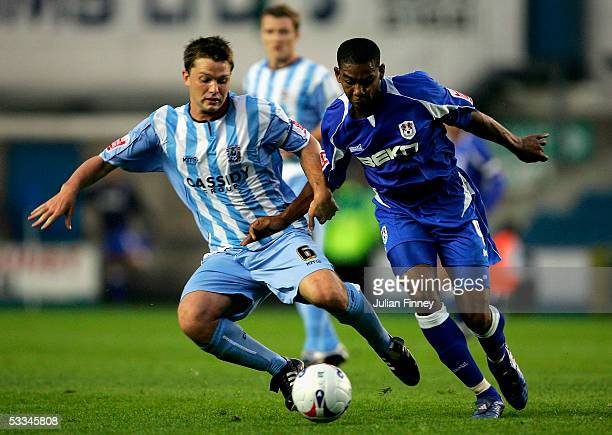 Stephen Hughes of Coventry City battles with Marvin Elliott of Millwall during the CocaCola Championship match between Millwall and Coventry City at...