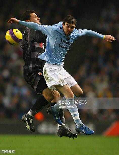 Stephen Ireland of Manchester challenges in the air with Graeme Murty of Reading during the Barclays Premier League match between Manchester City and...