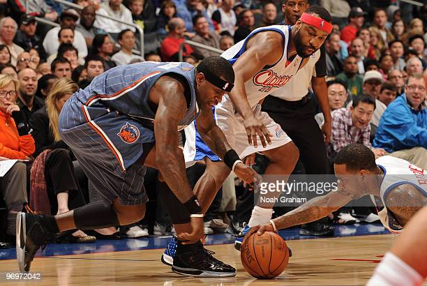 Stephen Jackson of the Charlotte Bobcats reaches for a loose ball against Baron Davis and Rasual Butler of the Los Angeles Clippers at Staples Center...