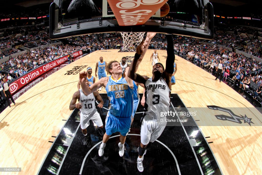 Stephen Jackson #3 of the San Antonio Spurs goes to the basket against <a gi-track='captionPersonalityLinkClicked' href=/galleries/search?phrase=Timofey+Mozgov&family=editorial&specificpeople=3949705 ng-click='$event.stopPropagation()'>Timofey Mozgov</a> #25 of the Denver Nuggets during a pre-season game on October 12, 2012 at the AT&T Center in San Antonio, Texas.