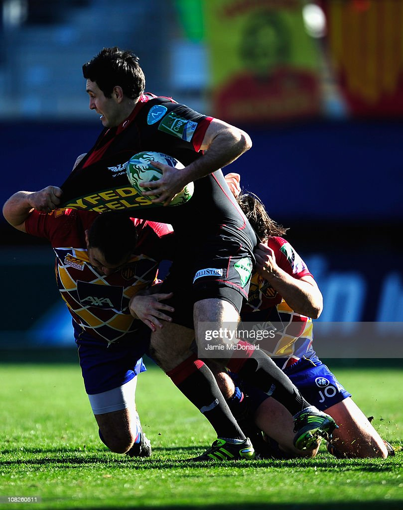 Stephen Jones of Scarlets is tackled by Knoyle Tavis and Mas Nicolas during the Heineken Cup Pool 5 match between Perpignan and Scarlets at the Stade...