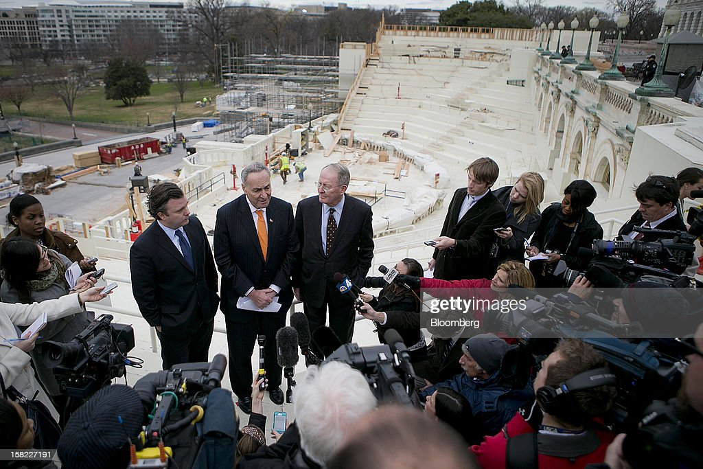 Stephen Kerrigan, chief executive officer of the Presidential Inaugural Committee, left to right, Senator <a gi-track='captionPersonalityLinkClicked' href=/galleries/search?phrase=Charles+Schumer&family=editorial&specificpeople=171249 ng-click='$event.stopPropagation()'>Charles Schumer</a>, a Democrat from New York, and Senator <a gi-track='captionPersonalityLinkClicked' href=/galleries/search?phrase=Lamar+Alexander&family=editorial&specificpeople=211236 ng-click='$event.stopPropagation()'>Lamar Alexander</a>, a Republican from Tennessee, hold a news conference next to construction of the platform being built on the west front of the U.S. Capitol in preparation for the inauguration ceremony of U.S. President Barack Obama in Washington, D.C., U.S., on Tuesday, Dec. 11, 2012. The presidential inauguration ceremony will take place on Jan. 21, 2013. Photographer: Andrew Harrer/Bloomberg via Getty Images