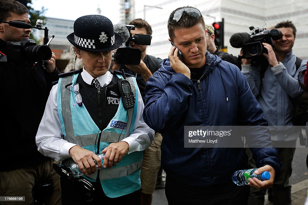 Stephen Lennon aka Tommy Robinson, leader of the English Defence League, discusses plans with a police liasion officer before the group march to Aldgate by EDL supporters on September 7, 2013 in London, England. The EDL far-right organisation have had restrictions placed on the march by the Metropolitan police due to the fear of 'serious public disorder', but it will still proceed to the edge of Tower Hamlets, which is home to a large population of ethnic minorities.