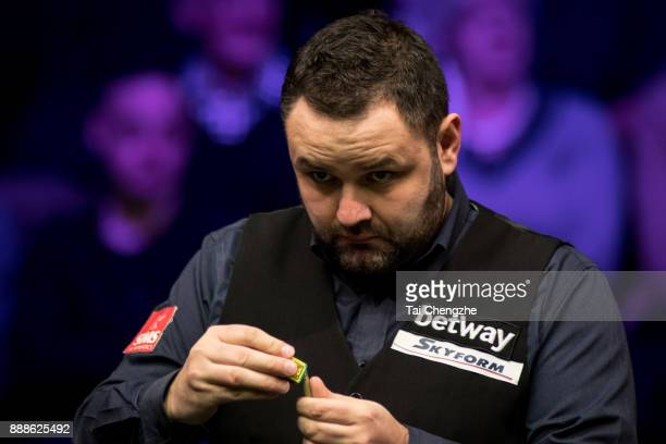 Stephen Maguire of Scotland chalks the cue during his quarterfinal match against Joe Perry of England on day 12 of 2017 Betway UK Championship at...