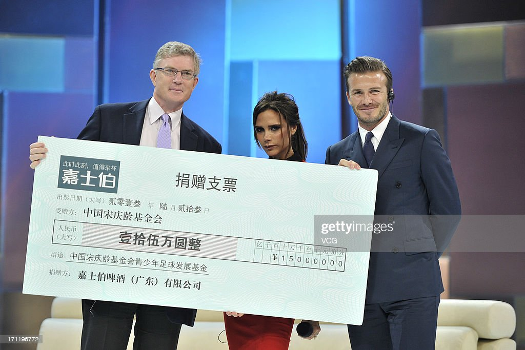 Stephen Maher, CEO of Carlsberg China, <a gi-track='captionPersonalityLinkClicked' href=/galleries/search?phrase=Victoria+Beckham&family=editorial&specificpeople=161100 ng-click='$event.stopPropagation()'>Victoria Beckham</a> and <a gi-track='captionPersonalityLinkClicked' href=/galleries/search?phrase=David+Beckham&family=editorial&specificpeople=158480 ng-click='$event.stopPropagation()'>David Beckham</a> pose with a cheque for 150, 000 Yuan (around 15, 730 GBP or 24, 264 USD) donated to the China Soong Ching Ling Foundation for the development of football by Carlsberg China during China Central Television show on June 23, 2013 in Beijing, China.