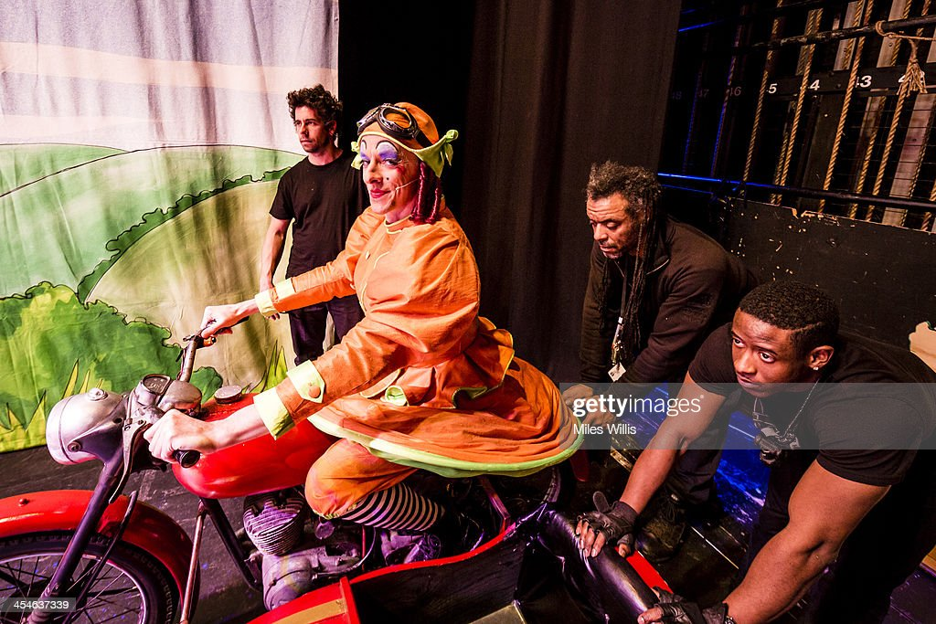Stephen Matthews playing 'Dame' sitting on a motorbike and sidecar waits for crew members to push him onstage during the Puss in Boots pantomime at the Hackney Empire on December 6, 2013 in London, England.