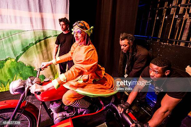 Stephen Matthews playing 'Dame' sitting on a motorbike and sidecar waits for crew members to push him onstage during the Puss in Boots pantomime at...