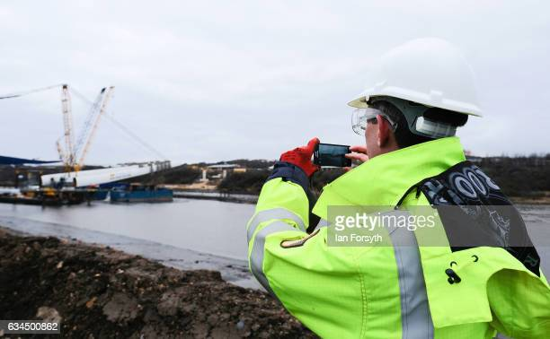 Stephen McCaffrey Project Director for Farrans Victor Buyck Joint Venture takes a photograph on his phone as the final 100 metre centrepiece of...