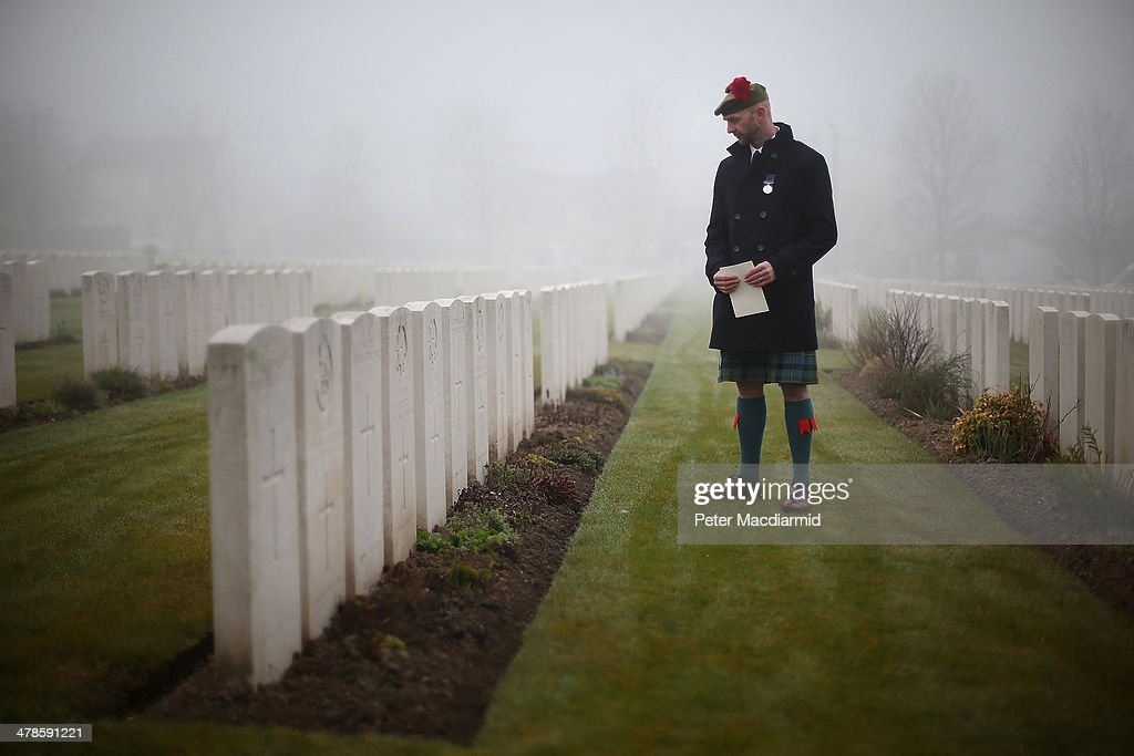 Stephen McLeod, great step nephew of World War One soldier Private William McAleer looks at headstones before a re-burial ceremony at Loos British Cemetery on March 14, 2014 in Loos-en-Gohelle, France. Almost 100 years after they were killed in action in the World War One battle of Loos in 1915, twenty British soldiers have been re-interred in the Commonwealth War Graves Commission Loos British Cemetery in Northern France. Private William McAleer, from the 7th Battalion the Royal Scottish Fusiliers, was found with his identity disc, but others found with him remain unidentified and have been buried as soldiers Known unto God . However, among the other soldiers are a Northumberland Fusilier, a further six Royal Scottish Fusiliers, a member of the York and Lancaster Regiment, two Queens Own Cameron Highlanders and nine others for whom no regiment has been identified.
