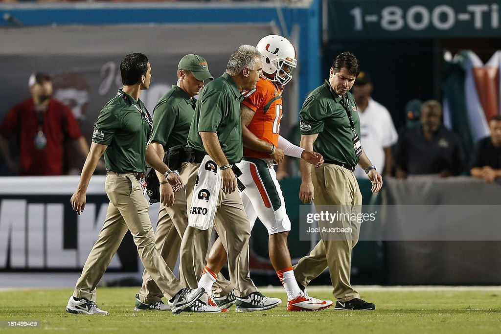 Stephen Morris #17 of the Miami Hurricanes is helped off the field after being injured during first quarter action against the Savannah State Tigers on September 21, 2013 at Sun Life Stadium in Miami Gardens, Florida. Miami defeated Savannah State 77-7.