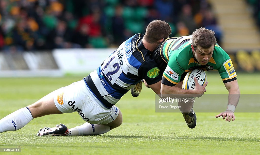 Stephen Myler of Northampton is tackled by Ollie Devoto during the Aviva Premiership match between Northampton Saints and Bath at Franklin's Gardens on April 30, 2016 in Northampton, England.